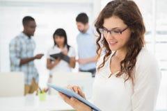 Lächelnde Geschäftsfrau, die Tabletten-PC verwendet Stockbild
