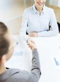 Lächelnde Geschäftsfrau zwei, die Hände im Büro rüttelt Lizenzfreie Stockfotografie