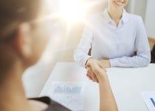 Lächelnde Geschäftsfrau zwei, die Hände im Büro rüttelt Stockbild