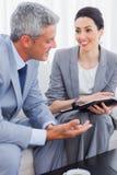 Lächelnde Geschäftsleute, die zusammen an Sofa arbeiten und sprechen Stockbilder