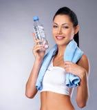 Lächelnde gesunde Frau mit Flasche Wasser Stockfotos