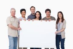 Lächelnde Gruppe, die leeres Zeichen zusammenhält Stockfotografie