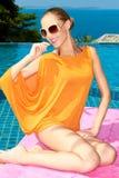 Lächelnde hübsche Frau in der orange Sommer-Ausstattung Stockbild