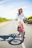 Lächelnde hübsche vorbildliche Aufstellung beim Reiten des Fahrrades Stockfotografie
