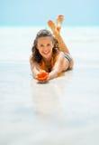 Lächelnde junge Frau auf dem Seeufer und -c$zeigen des Oberteils Stockbild