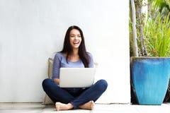 Lächelnde junge Frau, die auf Boden mit einem Laptop sitzt Stockfoto