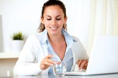 Lächelnde junge Frau, die ein Glas anhält Lizenzfreie Stockbilder