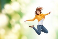 Lächelnde junge Frau, die hoch in einer Luft springt Stockfoto