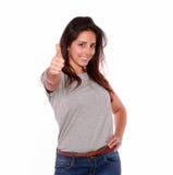 Lächelnde junge Frau, die Ihnen Daumen aufgibt Stockfoto