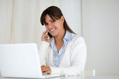 Lächelnde junge Frau, die Sie unter Verwendung des Laptops betrachtet Stockfotografie