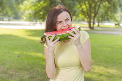 Lächelnde junge Frau, die Wassermelone isst Stockbilder