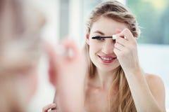Lächelnde junge Frau, die Wimperntusche anwendet Lizenzfreie Stockfotografie