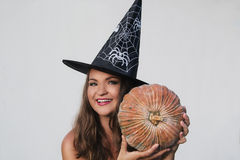 Lächelnde junge Frau im Halloween-Hexenhut mit Kürbis Stockbild