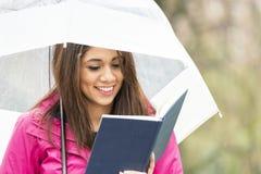 Lächelnde junge Frau mit Regenschirm liest Buch im Park Stockbild