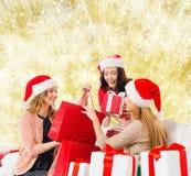 Lächelnde junge Frauen in Sankt-Hüten mit Geschenken Stockfotos