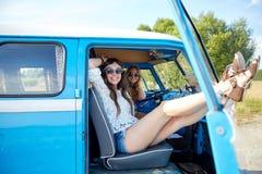 Lächelnde junge Hippiefrauen, die Mehrzweckfahrzeugauto stillstehen Lizenzfreies Stockbild
