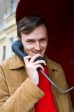 Lächelnde junge Männer, die durch Telefon sprechen Stockfoto