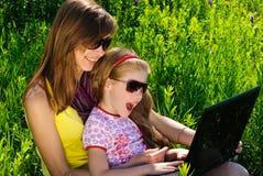 Lächelnde junge Mutter mit kleiner Tochter Stockbilder