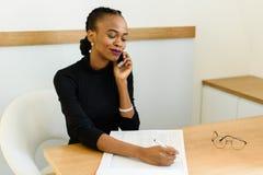 Lächelnde junge schwarze Geschäftsfrau am Telefon, das Kenntnisse im Büro nimmt Stockfoto