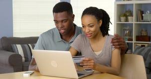 Lächelnde junge schwarze Paare unter Verwendung der Kreditkarte, zum des on-line-Kaufs abzuschließen Stockbild