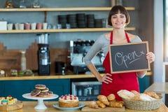 Lächelnde Kellnerin, die Schiefer mit offenem Zeichen zeigt Stockbilder