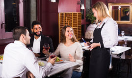 Lächelnde Kellnerin und Gäste am Tisch Lizenzfreie Stockbilder