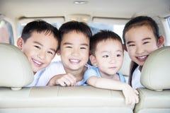 Lächelnde Kinder, die mit dem Auto reisen Stockbild