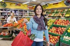 Lächelnde Kunden-tragende Einkaufstasche im Frucht-Speicher Stockfotos