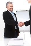 Lächelnde Leute, die Hände im Büro rütteln Lizenzfreie Stockfotografie