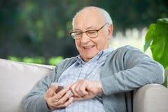 Lächelnde älterer Mann-Versenden von SMS-Nachrichten durch Stockbilder