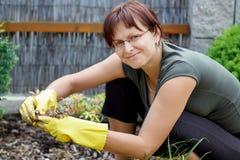 Lächelnde Mittelalterfrau, die am sonnigen Tag im Garten arbeitet Lizenzfreies Stockbild