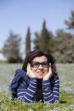 Mittlere gealterte Frau, die auf Gras sich entspannt Stockbilder