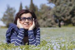 Mittlere gealterte Frau, die auf Gras sich entspannt Stockfoto