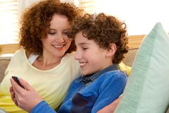 Lächelnde Mutter, die zu Hause mit ihrem Sohn sitzt Stockfotos