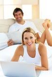 Lächelnde Paare, die auf Bett unter Verwendung des Computers liegen Lizenzfreies Stockbild