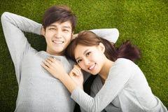 Lächelnde Paare, die auf grünem Gras sich entspannen Stockfoto