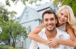 Lächelnde Paare, die über Haushintergrund umarmen Lizenzfreie Stockfotos