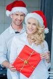 Lächelnde Paare, die ein rotes Weihnachtsgeschenk halten Stockbild