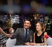 Lächelnde Paare, die für Abendessen mit Kreditkarte zahlen Stockbild