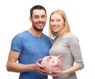 Lächelnde Paare, die großes Sparschwein halten Lizenzfreie Stockbilder