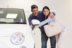 Lächelnde Paare, die innerhalb eines Autos schauen Stockbild