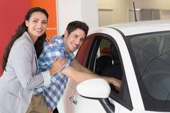 Lächelnde Paare, die innerhalb eines Autos schauen Stockfoto