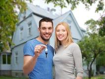 Lächelnde Paare, die Schlüssel über Haushintergrund zeigen Stockbilder