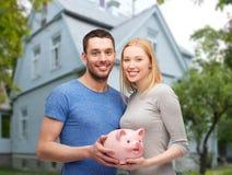 Lächelnde Paare, die Sparschwein über Haus halten Stockfoto
