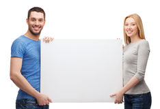Lächelnde Paare, die weißes leeres Brett halten Stockfotografie