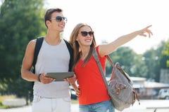 Lächelnde Paare mit Tabletten-PC und -rucksack in der Stadt Stockfoto