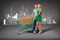 Lächelnde Paare mit Warenkorb und großem Kasten Lizenzfreies Stockfoto