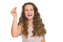 Lächelnde reißende Finger der jungen Frau Stockfoto