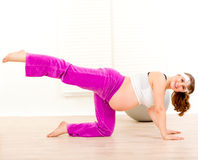 Lächelnde schwangere Frau, die Aerobicsübung tut Stockbild