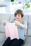 Lächelnde schwangere Frau, die Babykleidung hält Lizenzfreie Stockfotografie
